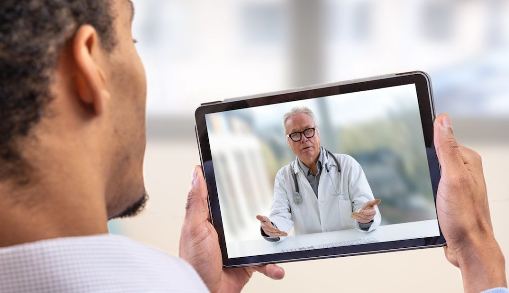 Doctor and Patient talking over tablet - telehealth.